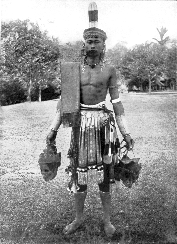 COLLECTIE_TROPENMUSEUM_Portret_van_een_Dajak_krijger_op_Borneo_met_twee_van_hoofddeksels_voorziene_schedels_in_zijn_handen_en_een_kleed_over_zijn_schouder_TMnr_60043379